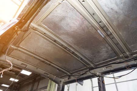The metal roof of the SUV with the sound insulation removed during interior repair is a replacement of the ceiling lining in auto service. Car salon tuning. Standard-Bild