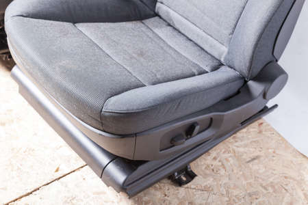 A close-up of the front seat of a car with a gray fabric textured pattern with plastic height adjustments taken before dry cleaning in a photo studio. Banco de Imagens