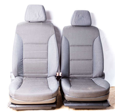 A pair of front row car seats made of gray fabric isolated on a white background in a photo studio shot from the interior of a auto before being replaced by a service or dry cleaning.