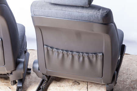 Rear view of car seats close-up upholstered back in gray leather with a storage box for storage in the service station before installation after dry cleaning.