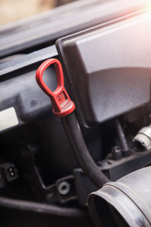 The dipstick for checking the oil level in black with a red handle close-up against the background of engine assemblies. A standard device stored under the hood of a car. Stockfoto