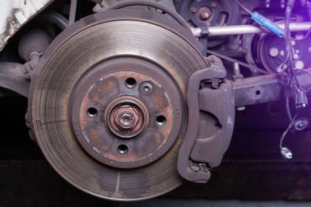 Close-up metal disk in blue backlight - main element of brake system. Friction surface for brake pads. When braking, the pads are pressed against the disk and, due to the friction force, stop rotation