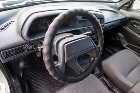 Novosibirsk, Russia - 05.20.2020: Control panel and the center console of Russian car with steering wheel and turn signal knobs and a wiper with gray air conditioning holes made of inexpensive plastic