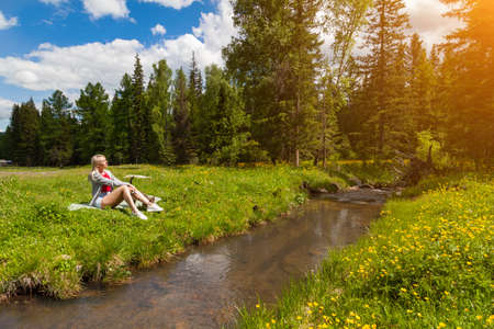 A blonde girl sits in a clearing against a forest and blue sky next to a stream, her eyes closing in the sun, a cat rubs against her legs. Halt during a walk in the Altai mountains. 版權商用圖片