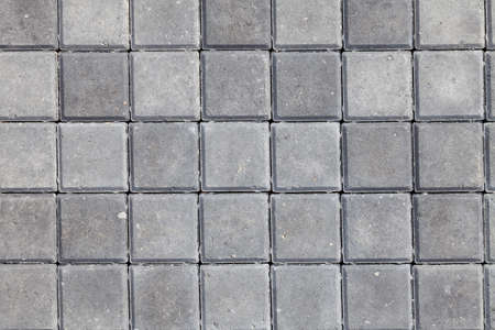 Background and texture of gray color from square paving granite tiles. Decor of roads and pedestrian streets.