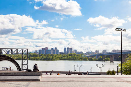 One man sits on bench and observes view from embankment to river, the metro bridge over it, houses under construction on opposite bank, a summer day in Novosibirsk against a blue sky and white clouds.