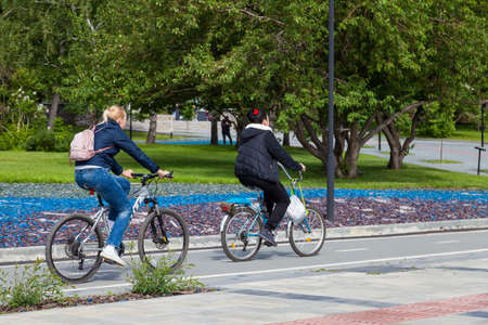 Novosibirsk, Russia - 06.06.2020: Two women spend a weekend in the park renting bicycles and ride a specially designated path against the background of green trees and decorative stone flowerbeds