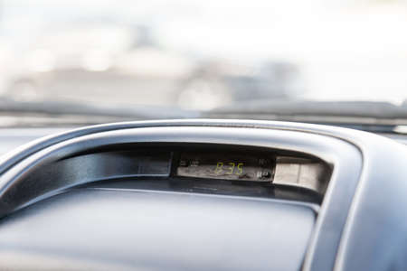 A close-up of the clock on the dashboard of a car, close-up, on gray plastic, with an electronic dial with backlit green numbers. 免版税图像