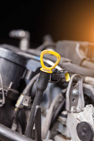 The dipstick for measuring the oil level in black with a yellow handle close-up on the background of engine assemblies. The standard device is stored under the hood of the car.