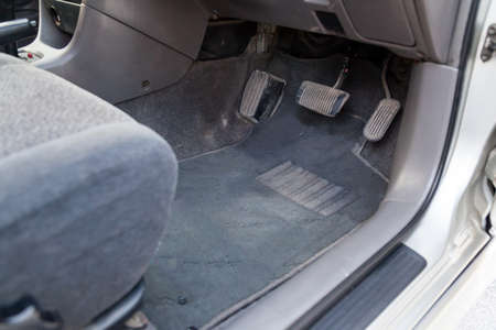 Gray cloth car mat in the interior of a Japanese sedan with three pedals gas, brake and clutch in a car service after dry cleaning.