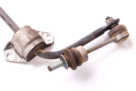 Close-up metal stabilizer rack on a white background in a second-hand photo studio with rust for replacement during repair or for sale at an auto-parsing. Imagens