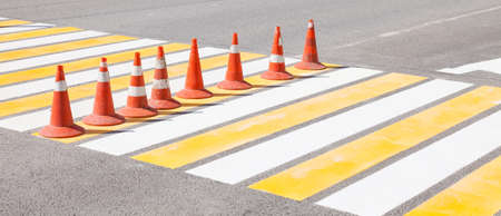 Drawing new white and yellow markings on the pedestrian crossing during road works with orange cones to indicate the bypass of fresh paint.
