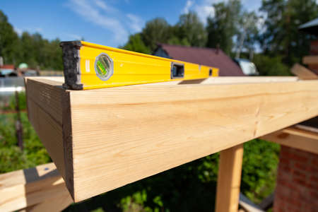 Wooden timber on summer day in village cottage in open air against a background of sky, green trees and grass with a water level lying on a beam to determine deviations in horizontal surface location.
