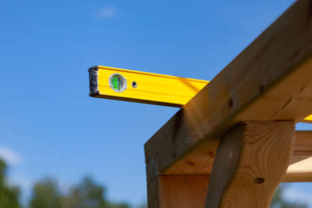 A wooden beam made of fresh timber with yellow carpentry tools - a water level for accurate marking on a summer day against the sky and green tree tops.