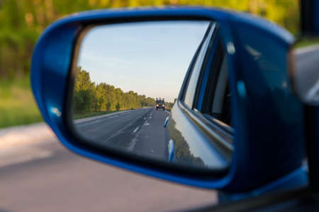 Rear view in the side mirror of a blue sedan with the reflection of a gray truck on an asphalt road on a summer day with green trees on the sides of the highway.