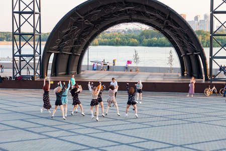 Novosibirsk, Russia - 03/07/2020: A group of girls is recording a dance for the kippah on the embankment of the square against the background of the stage, a guy videographer is filming.