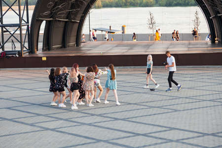 Novosibirsk, Russia - 07.03.2020: A group of girls is rehearsing a dance on the embankment of the square in front of the stage, a guy videographer takes a video camera. 新聞圖片