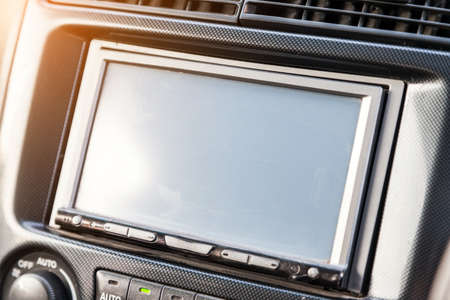 The central control console on the panel inside the car close-up with a computer display, an audio system and a radio in gray and black plastic. On-board navigator screen.