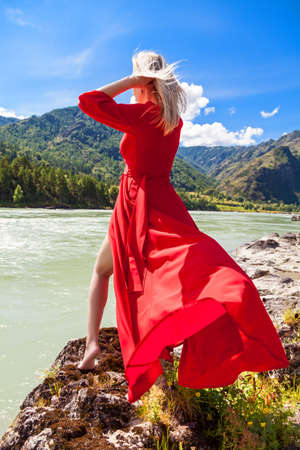 A blonde woman with fluttering hair and a red dress in the wind stands on the banks of the Katun River in the Altai mountains, feeling freedom and unity with nature. Archivio Fotografico