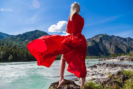 Blonde woman in long red dress fluttering in wind stands barefoot on rocky shore with one leg outstretched against background of mountains, blue clouds and birch-tree river in Altai. View from back Archivio Fotografico