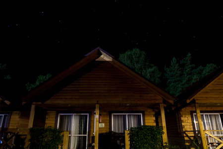 Cozy wooden houses at the tourist base at night against the background of the starry sky and trees in the Altai mountains in summer. Country rest in comfortable conditions. Archivio Fotografico