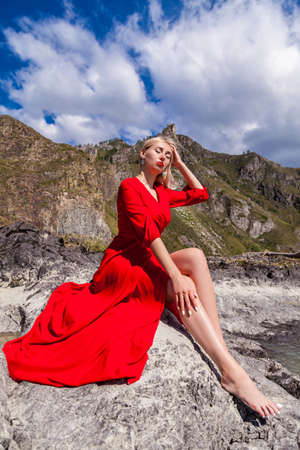 A blonde woman in a red long dress sits on the stone bank of the river against the backdrop of mountains with closed eyes and make-up on her face and runs her hand along her outstretched long legs.