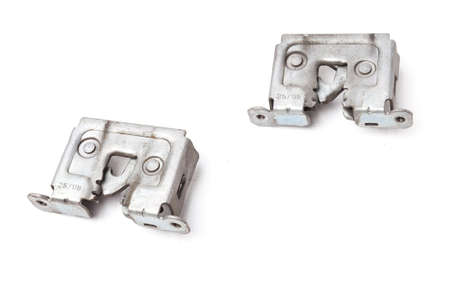 A pair of metal locks separately on a white isolated background in a photography studio, aluminum hood parts for replacement during repair or auto-parsing sale.