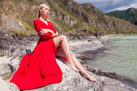 Blonde woman in red vintage dress with earrings in ears, arms folded on her chest, hugging herself, sits stretching her long legs on the stones on banks of Katun river against background of mountains Archivio Fotografico