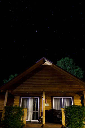 Ð¡ozy evening in country house made of timber at tourist base in Gorny Altai on a summer night against the background of the black sky and stars. A weekend in isolation with a loved one in the forest. Archivio Fotografico