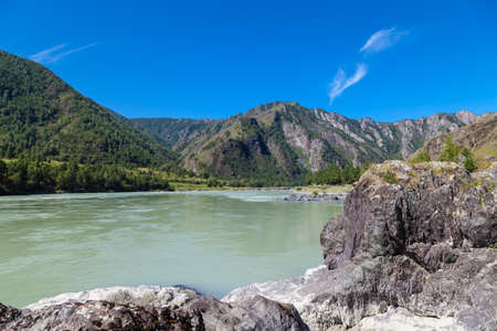 The Katun River is a favorite place for rafting in the Altai mountains on a sunny summer day under the blue sky in a deserted place. Tourist place in Siberia.