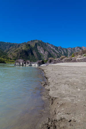 A river bank with a sandy beach against the background of a mountain covered with green trees on a summer day in Altai in a deserted place. Country rest.