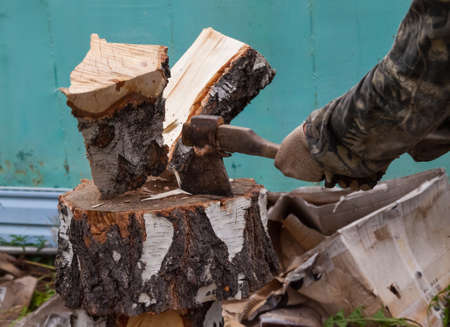 A log split in half with an ax on a deck with male hands in cloth gloves and a camouflage jacket in the backyard. Household work to prepare for the winter.