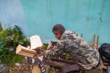 A man in a camouflage suit chops wood with an ax with a wooden handle and an iron blade in the village or at the dacha next to a metal fence for kindling a stove in a house. Archivio Fotografico