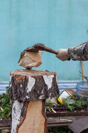 A log of wood chopped into an ax, smashed against a deck by a man's hand in fabric gloves. Household work in a private house or in the country.