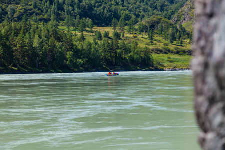 Departing rafting tourists on a rubber blue boat along a mountain turquoise river against the background of a high green bank with coniferous trees.