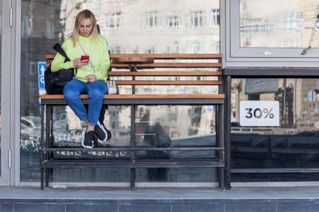 Street style girl in neon blue jeans hoodie and sneakers with a backpack sits on a bench near a coffee shop and looks at the phone in her hands. Young woman at a bus stop waiting for public transport.