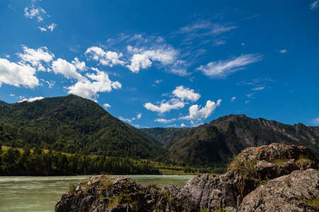 A picturesque landscape from the rocky bank of the Katun mountain river of turquoise color in Altai against a background of blue sky and white clouds. Tourist place in Siberia.