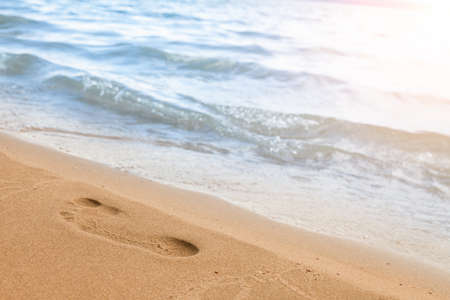Close-up of the beach shore with a man's footprint on the yellow sand along the line of the blue sea wave on a summer sunny day. Background for advertising travel or tourist vacation. 版權商用圖片 - 155892817