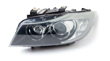 Stylish xenon right headlight of a German car - optical equipment with a lamp inside on a white isolated background. Spare part for auto repair in a car workshop. Standard-Bild