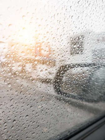 Background from drops of water and rain on a car glass window on a cloudy autumn day. Calmness, freshness, weather.