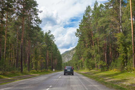 Asphalt road in Altai mountains on summer day against background of hilltops and green coniferous forest with an SUV car moving through the trees. Free path during a vacation outside city in nature. 新聞圖片