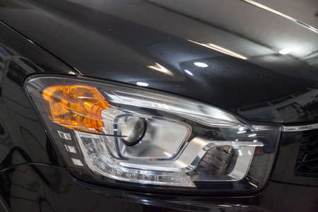 A view of a dark blue car headlight after cleaning and polishing before being sold. Large vehicle lamp with xenon lens. Auto-parsing car in the garage.