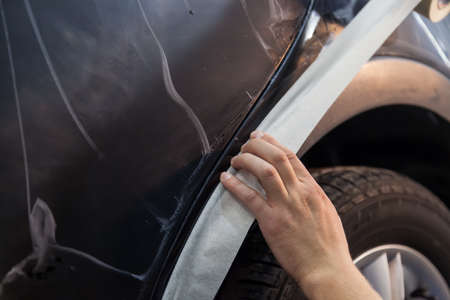 Covering plastic part of wing of the body of a black car with a protective white tape to prevent the ingress of the polishing compound in order to avoid stains and prepare for repair and maintenance.