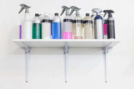 Shelf on a white wall in a workshop with a working tool - containers with sprayers and bottles with multi-colored liquids for cleaning, polishing and wiping cars. 版權商用圖片