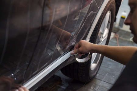 Master pastes over plastic part of threshold of black car body with protective white tape to prevent ingress of polishing compound in order to avoid streaks and prepares it for painting in workshop.