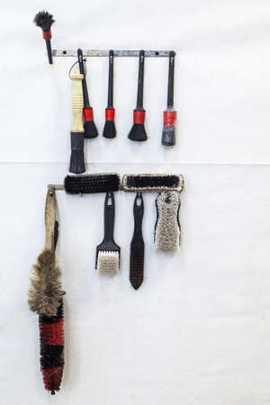 A set of black and red brushes hanging on a shelf on a white wall, a set of tools for working in a car workshop for painting, polishing and dry cleaning. 版權商用圖片