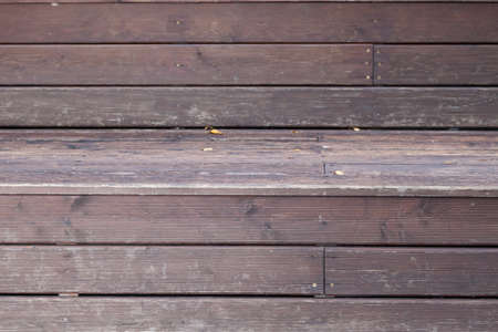 Close-up of a veranda wall made of brown and gray wooden planks with relief as a background for an autumn decor or billboard.