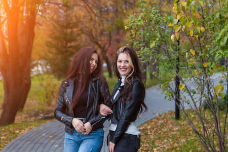 Two girlfriends, students laugh and stand on the path in jackets and jeans while walking in the park against the background of trees with yellow leaves in an autumn day. 版權商用圖片