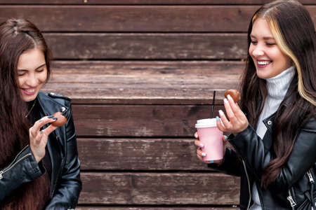 Two young brunette women with long hair in black leather jackets and sweater sit on bench and drink coffee while holding cups and cookies in their hands and smile on background of brown wooden boards