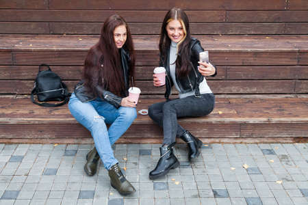 Two young brunette women sit in park in autumn on a wooden bench and take a selfie on the phone in black jackets and smile and hold coffee cups in their hands. Best friends communicate via video link.